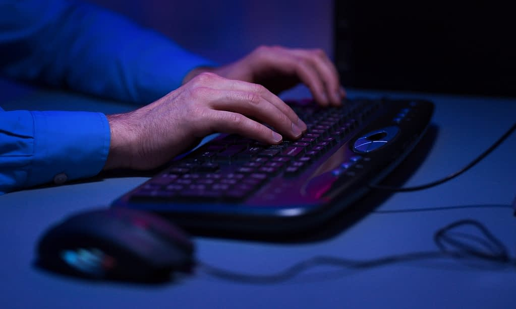 Gamer actively pushing buttons on keyboard, playing games